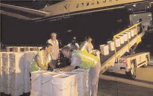 A ground crew unloads more than 17 tons of silver coins recovered from the
