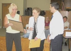 Retired MCHC director Lois A. Baker (center) and State Sen. Daniel Mongiardo looked on Monday night as State Rep. Leslie Combs read from a citation honoring Baker for her accomplishments while in charge of the company.