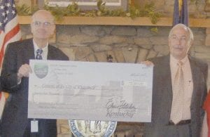 Kentucky Transportation Secretary Bill Nighbert handed a check to Whitesburg Mayor James W. Craft. The city will get $175,600 for a pedestrian bridge to connect the paid parking behind the courthouse to the free parking lot located next to the Veterans Memorial Park. The city also received $75,000 to resurface various roads.