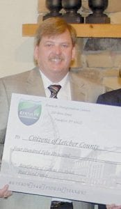 Letcher County Judge/Executive Jim Ward, above left, received a check for $450,000 in road bond funds from the Kentucky Transportation Cabinet.The City of Jenkins received $600,000 to help build a 3,352 square-foot welcome center which will serve as the only welcome center in southeastern Kentucky and on US 23. Pictured above right, from left, are Jenkins Mayor Charles Dixon, Jenkins Council Member Becky Terrill, Commissioner of the Department of Transportation Ginger Wells, who is a Letcher County native, and Nighbert.