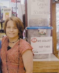 Pam Cornett, a director for a Ronald McDonald care mobile dental program in Hazard, volunteers her time to take pop tabs collected at the Whitesburg IGA Food Word to the Ronald McDonald House.
