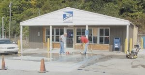 GETTING READY FOR MORE CUSTOMERS -  Uda Pharis (pictured at left) and Matt Campbell, both of Litchfield, Kentucky, power washed paint off of the sidewalk in front of the new Mayking/Millstone/Thornton Post Office on August 20. (Photo by Sally Barto)