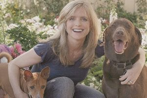 Actress Courtney Thorne-Smith is seen posing with her dogs, Ed, left, and Norman at home recently in Los Angeles. Thorne-Smith, whose acting career includes her breakout role in