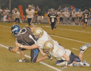 WRAPPED UP -  Two Hazard defenders teamed up to tackle Letcher County Central's Kevin Wurschmidt early in the Cougars' season-opening loss to the Bulldogs at Ermine last week. (Photo by Chris Anderson)