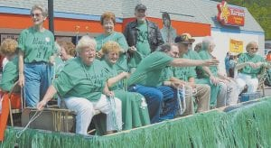 Members of the Jenkins High School Class of 1957 threw beads from the float on which they were riding during the parade through downtown Saturday morning.