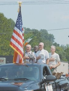 World War II veterans riding through the parade paused to pay tribute to fallen soldiers while Taps was being played.