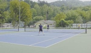 NEW SURFACE -  Ray Ison, left, Ryan Ison and Shaun Marcum were hitting tennis balls Monday afternoon on the newly-refurbished tennis courts in West Whitesburg.