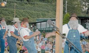 Tim Hall, far right, waved to the camera Friday while performing with the Soggier Bottom Boys, a novelty act which has delighted Neon Days Festival crowds for several years. Fellow band members Chine Blair, Darrell Wright and Dave Perry are shown from left.