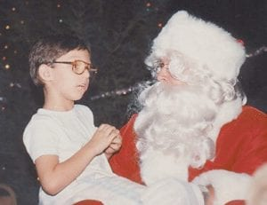 Dressed as Santa Claus during a Christmas parade sponsored by the Neon Area Jaycees, Hall spoke with young Aaron Polis in this file photo.