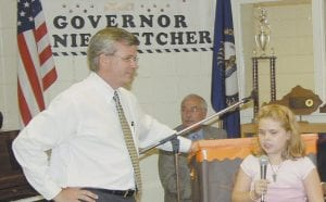 GETS NEW COMPUTER -  Melissa Baker, a student in third grade at Burdine Elementary School, thanks Governor Ernie Fletcher (left) after Fletcher presented her with a rebuilt computer during a ceremony in Whitesburg last week. Seated behind Baker and Fletcher is Whitesburg Mayor James W. Craft. (Photo by Sally Barto)