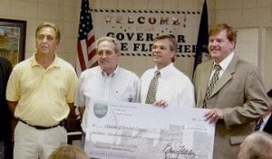 Gov. Ernie Fletcher presented the Letcher County Fiscal Court with a check for $1,009,000 to replace a one-lane bridge at Millstone which spans the North Fork of the Kentucky River on KY 805. Pictured from left are District Two Magistrates Archie Banks, District One Magistrate Bob Lewis, Fletcher and Judge/Executive Jim Ward.