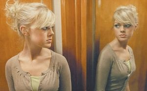 Cheyenne Cawthon, of Quincy, Ill., looks at her reflection in a mirror. Because of her general anxiety disorder and body dysmorphic disorder, what she sees in the mirror does not reflect reality. (AP Photo/The Quincy Herald Whig)