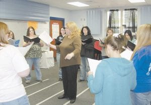 Letcher County Central High School Choral Director Jessica Sparks (pictured center) leads the choral ensemble. Pictured farthest away are Cortney Roberts, Tasha Howard, Auri Bolen, Martha Frazier, Brittany Combs and Natasha Gibson. Pictured closest to camera are Ciarra Brock, Olivia Trouxel and Tiffany Back.