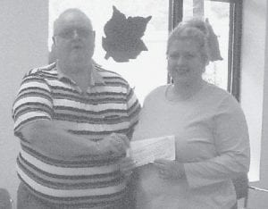 DONATION -  Kester Halcomb of the Whitesburg Lions Club, presents Beth Bowling, director of the Esta Craft Conway Center for Women and Children, with a donation and household and personal items for the residents of the center. The items were donated by Lions Club members.