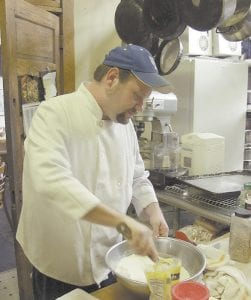 CHEF AT WORK -  James Feltner worked to mix the ingredients of a dish he was preparing Monday. After graduating from culinary school and working in Florida, Feltner is now plying his trade in Letcher County, where he grew up. (Eagle photo)