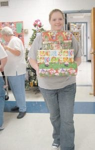 Thornton resident Tessa Fugate carried shoeboxes filled with toiletries, small toys and candy into the First Baptist Church in Whitesburg on Monday night. The filled boxes will be delivered to Operation Christmas Child, a project of Samaritans Purse headed by evangelist Franklin Graham, and then shipped to children all around the world who may not otherwise receive a Christmas gift. Finished gift boxes can be dropped off at the church now through Friday (November 16) between noon and 8 p.m., and from 10 a.m. to 6 p.m. on Saturday. People can drop off shoeboxes on Monday (November 19) between 10 a.m. and 6 p.m. Last year 8,831 shoeboxes were collected at the Whitesburg church. The goal for this year is to collect 9,000 shoeboxes. (Eagle photo)