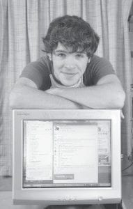 INSTANT MESSENGER -  Lewis Grove, 19, leaned on his computer monitor at his home in Heath, Ohio, recently. Grove has used instant messages to arrange dates and to break-up with girlfriends. (AP Photo/Timothy E. Black)
