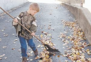 HELPING GRANDPA -  Noah Campbell, 5, took advantage of a warm afternoon last week to help his grandfather, Robbie Campbell, rake leaves that were covering a driveway beside Letcher Funeral Home in Whitesburg. (Eagle photo)