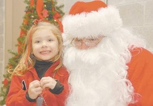 MAKIN' HIS LIST -  Santa Claus visited Letcher County over the weekend to ask boys and girls what he should bring along for them when he returns on December 25. While he was here on Saturday, Santa rode on a fire truck in the Jenkins Christmas Parade before meeting 150 children, including Madison Polly, who is pictured above. (Photo by Chris Anderson)