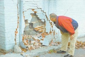 Cavalier Cafe owner Joe Eddie Eversole inspected the damage to the wall of his building after the mishap that left a cook badly injured.
