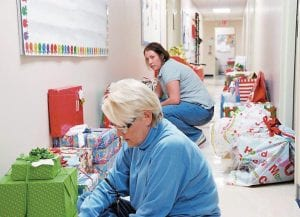 SORTING GIFTS -  Glenda Banks (foreground) and Holly Hammock were busy this week at the Cabinet for Families and Children in Ermine sorting through toys and clothing that will be given away to needy children. (Photo by Chris Anderson)