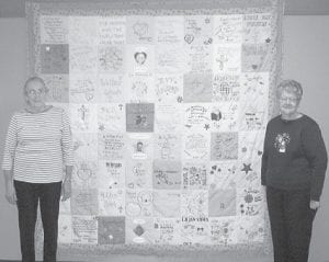 MEMORY QUILT -  Paulene Bailey (left) and Coleene Hart of the Ermine Senior Citizens Center stand beside a memory quilt they pieced and quilted. The quilt was displayed at the annual memorial service of Letcher County Hospice of the Bluegrass. Each square of the quilt was designed by a hospice family member in one of the five counties served by Hospice of the Bluegrass - Mountain Community.