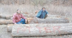 Dave Potter, left, and his cousin, Mark Combs, sit on fallen white oaks that were allegedly chopped down by a timber thief at the family's property at Craft's Colly. (AP Photo/Samira Jafari)