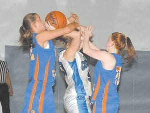 TANGLED UP IN BLUE -  Letcher County Central High School girls' basketball player Brittany Sexton fights for control of a rebound against Pike County Central's Bethany Howell (left) and Abbey Coleman (right). Visiting Pike Central won the game, 75-42. (Photo by Chris Anderson)