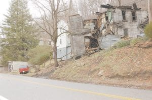 ROAD HAZARD -  The remains of an old coal camp house located between Jenkins and Dunham are creating a traffic hazard on Kentucky Highway 805, which was covered by debris last week after the structure started sliding down the hillside.
