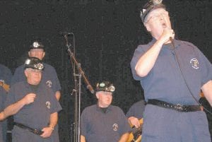 SINGING MINERS -  Men of the Deeps, a choir of working and retired coal miners from the island of Cape Breton in Nova Scotia, Canada, performed a public concert on the evening of Feb. 5 at Letcher County Central High School in Whitesburg. Letcher Schools Superintendent Anna Craft said a large and enthusiastic crowd attended the public performance. Craft said Men of the Deeps received a standing ovation from Letcher Central students after performing for them earlier in the day. (Photo by Becky Johnson)