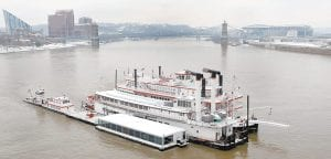 The Mike Fink riverboat restaurant, center, towed by two escort boats on either side, headed up the Ohio River from Covington, Ky., on Feb. 23. The 72-year-old riverboat restaurant, listed on the National Register of Historic Places, was making a 160-mile trip to a dry dock in South Point, Ohio, where it will have a new welded steel hull installed as part of a $2 million renovation. (AP Photo/The Enquirer/Ernest Coleman)