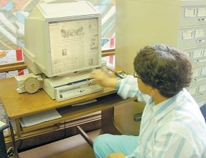 Lena Tidal, director of Letcher County Public Libraries, last week demonstrated how to use the new Microfilm ScanPro 400i. She said people will be able to email themselves images with the $4,000 machine. (Photo by Sally Barto)