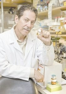 In this photo provided by the Salk Institute, Ron Evans is seen holding a vial of a drug that boosts the effects of exercise in mice at the Salk Institute for Biological Studies in La Jolla, Calif.