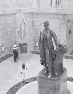 Tourists posed for pictures in front of the Jefferson Davis statue in the Capitol Rotunda as a statue of Abraham Lincoln towers in the foreground in Frankfort last week. (AP Photo/Ed Reinke)