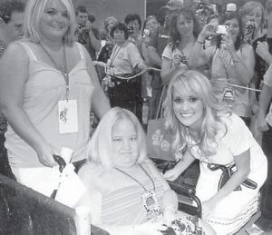 BRITTANY BROCK (above center) and her cousin Jessica Sexton (left) met singer Carrie Underwood (right) at the Country Music Festival, which Brittany Brock attends annually. Her mother, Debbie Brock, also attended the festival. Below, Brittany Brock recently traveled to Orlando and Destin, Fla., with her mother. This photograph was taken at Tybee Island, Ga. Pictured are (left to right) Keaton Day, Kianna Day, Brittany Brock, Jessica Sexton, and Jessica Ross, the fiancee of Brandon Brock, Brittany Brock's brother.