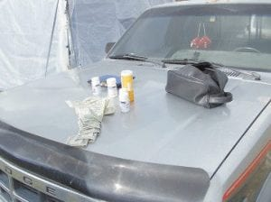 Prescription pill bottles and cash were placed on the hood of a pickup truck belonging to Thomas during Tuesday's bust.