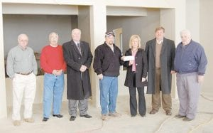Rick Hayes, TECO reclamation supervisor, presented Lana Polly Mullins, director of the Letcher County Health Department, with a check for $3,000 on December 5 in front of what will be the reception area of the new health department. Pictured from left are Whitesburg pharmacist Earnest Watts, a member of the Letcher County Health Department board of directors, Whitesburg Mayor James W. Craft, State Senator Johnny Ray Turner, Hayes, Mullins, Letcher Judge/Executive Jim Ward and District Five Magistrate Wayne Fleming. (Eagle photo)