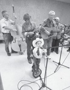 BLUEGRASS BOY —3-year old Jonathan Rader is seen playing bluegrass music with the group Driving Rain during a weekly bluegrass music jam session held at the