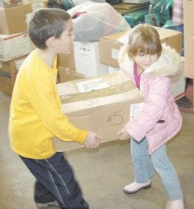 Six-year-old Rachel Hendrian (right) and her eight-year-old brother Kyle Hendrian helped carry boxes full of gifts Monday into the old Boone Moter Company building now owned by Appalshop.