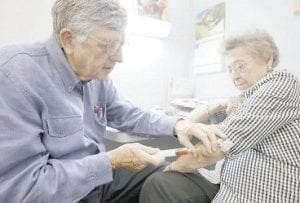 Dr. David Watson, left, drained the elbow of Dorothy Dean, 83, recently in Yoakum, Texas. Watson is the 2008 Country Doctor of the Year, presented by Staff Care. Like country doctors and house calls, family practitioners are a disappearing breed. (AP Photo)