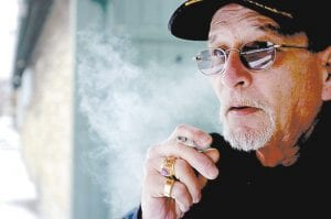 Gary Hilton is a bartender in Moline, Ill., one of many cities and counties which now ban smoking in the workplace. A new study says a similar smoking ban in Pueblo, Colorado has reduced the number of heart attacks there. Hilton was outside taking a break when this photo was taken. (AP Photo)