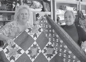 QUILTS ON DISPLAY — Debra Howell of Pike County (left) and Josephine Richardson, owner of The Cozy Corner in Whitesburg, hold an example of the hand sewn quilts which Richardson sells in her store. The Letcher County Tourism and Convention Commission will present an exhibit of quilts at the Harry M. Caudill Memorial Library from February 5 to 21.