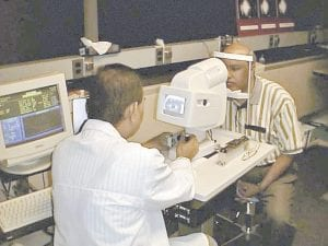 Dr. Manuel Datiles of the National Eye Institute, left, tests an eye device on NASA scientist Rafat Ansari. Ansari developed a device originally used in space-shuttle experiments that can help determine when the eye becomes vulnerable to developing cataracts. (AP/NASA)