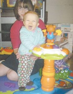 HAPPY BABY — Grace Anne Long, who will turn one on Saturday, plays under the watchful eye of sister Stephanie. Grace suffers from a disease that is almost always fatal.