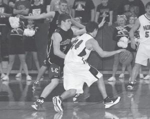 Letcher County Central freshman Logan Johnson did a good job of containing Knott Central's Tate Cox while guarding the 14th Region star, but Cox still managed to do his share of damage in the Cougars' loss to the homestanding Patriots last week. (Photo by Chris Anderson)