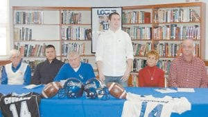 NOW A COLONEL — Charlie Banks, standing, signed a letter of intent last week accepting a scholarship offer to play football at Eastern Kentucky University in Richmond. Among those attending the signing ceremony were, from left, Letcher Central athletics director Ozz Jackson, Letcher Central head coach Hillard Howard, Banks's mother Tommye and father Steve.