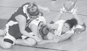 Lady Cougars Haley Whitaker and Tierra Baker wrestled a Knott County player for possession of the ball during Letcher Central's win over the Lady Patriots last week. See story, Page 10. (Photo by Chris Anderson)