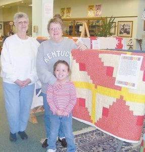 QUILT SHOW CONTINUES — The Festival of Quilts Exhibit, sponsored by the Letcher County Tourism Commission, is underway at the Harry M. Caudill Memorial Library in Whitesburg . The exhibit, which runs through February 28, features 51 hand-made quilts from quilters throughout Letcher County. Pictured above are, from left, Tourism Commission member Doriesa Adams, Bessie Shepherd, a volunteer, and Shepherd's granddaughter, Madison Grace Hurst.