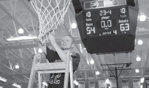 DISTRICT CHAMPS — Letcher County Central's Devon Blair took his turn at trimming the nets after the Cougars defeated Knott County Central for the championship of the 53rd District. (Photo by Chris Anderson)