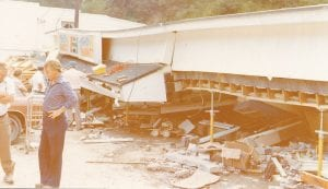 Above is the Thrifty Market, a store in downtown Jenkins that was destroyed after the water tank seen at left burst at the bottom on July 15, 1979, and sent 300,000 gallons of water onto the neighborhood below. An elderly doctor was killed when his home was splintered. Jenkins officials and residents are concerned that a natural gas well being drilled near the same location could cause a replacement tank to burst as well.